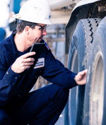Man performs maintenance on 18-wheeler truck.