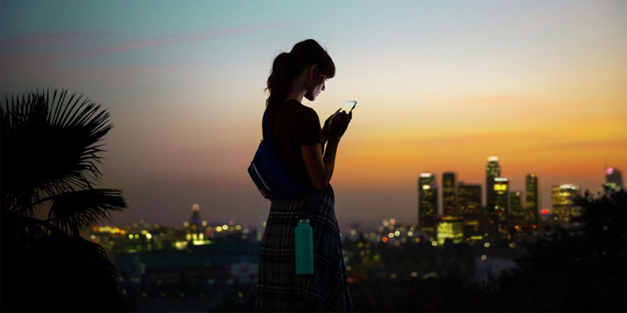 Woman using a 5G-enabled smartphone outside a connected cityscape