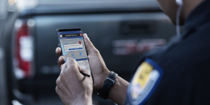 Police office enters data on Samsung smartphone