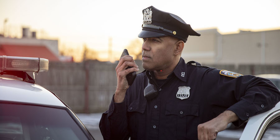 Police officer using push-to-talk smartphone next to cruiser