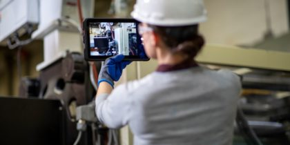 a worker performs a preventative maintenance inspection with a tablet