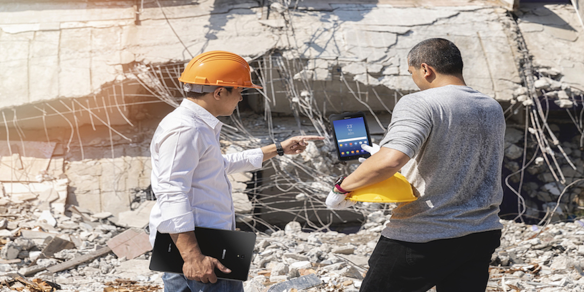 Two workers with hard hats use a tablet in the field
