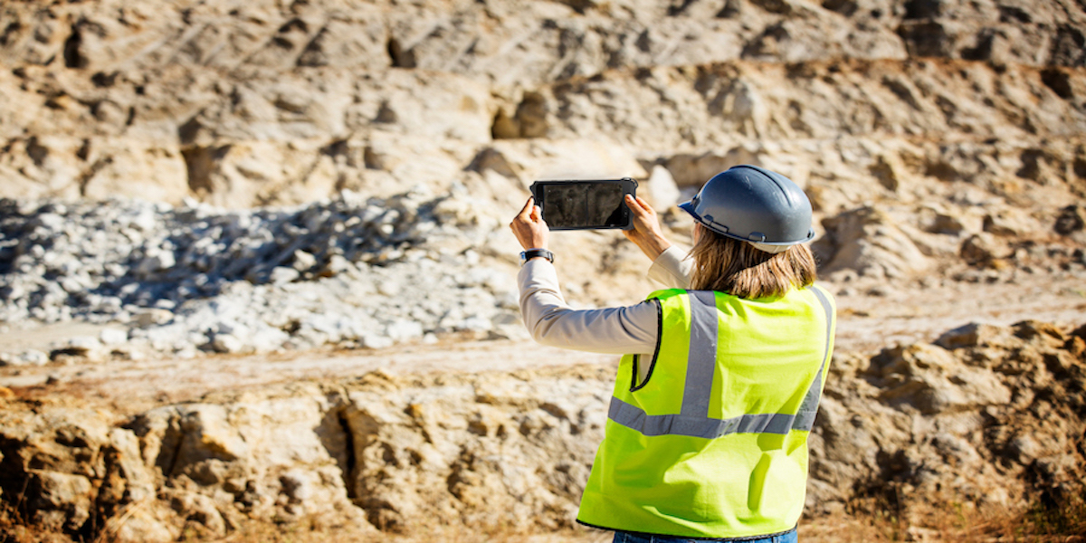 A worker in a safety vest and hard hat uses a tablet to take a photo