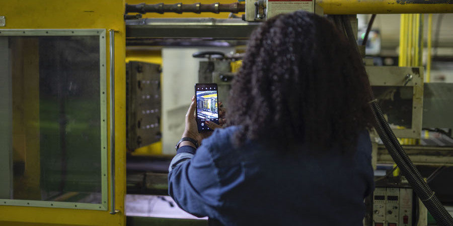 A manufacturing worker uses a Samsung Galaxy XCover Pro on the job