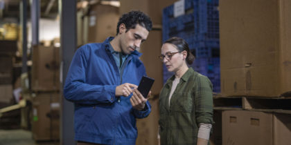 Two warehouse workers use a Samsung Galaxy XCover Pro for inventory management