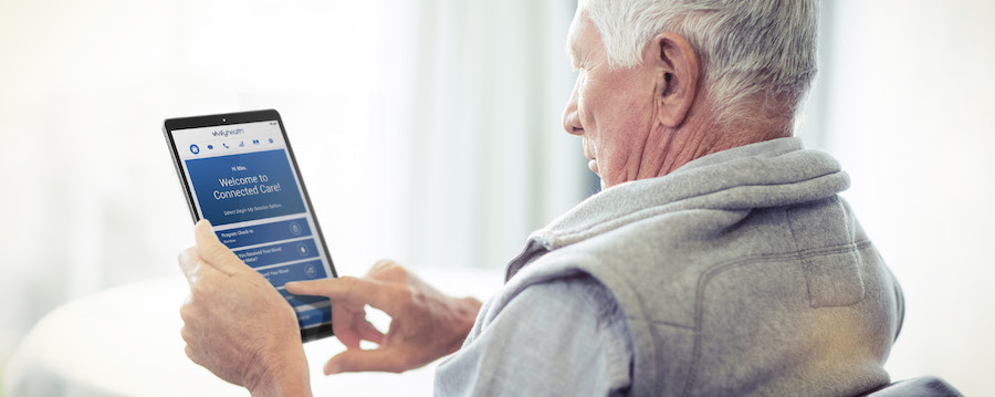 An older man uses a Samsung tablet to access a remote healthcare app from home