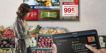 A customer shops for produce in front of digital signage displaying prices and specials